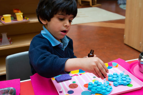 Nursery child doing a fine motor skill table top activity